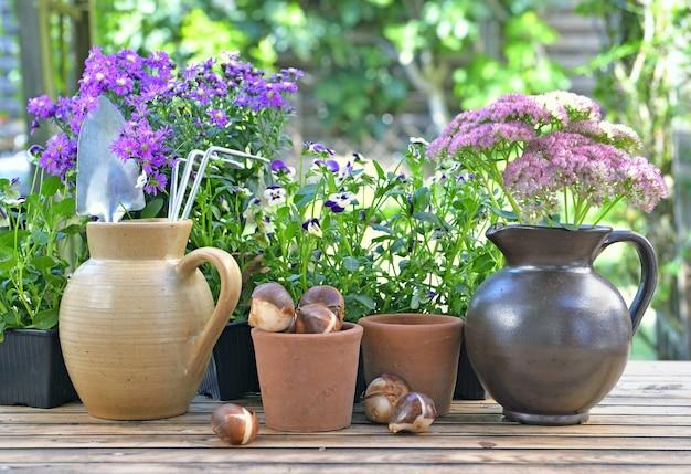 Tuingereedschap in een waterkan die met anderen op een tafel met bloemen en bollen in de tuin wordt geplaatst