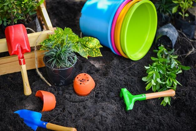 Tuingereedschap op de bodem klaar om bloemen te planten en kleine plant werkt tuinieren
