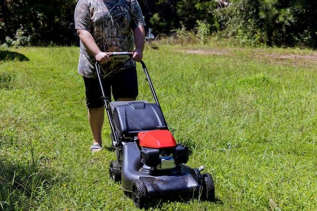 Tuinieren activiteit, grasmaaier die de grasmaaier maait in zonnige tuin