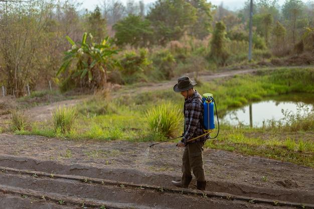 Tuinieren concept een jonge mannelijke boer die een chemisch bestrijdingsmiddel sproeit om te voorkomen dat de gewassen ongedierte krijgen.