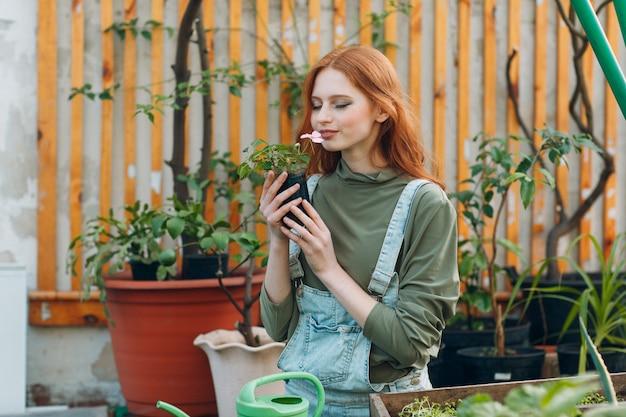Tuinieren concept. jonge mooie vrouw met bloempot ruikende bloem. spring home tuinplant.