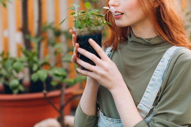 Tuinieren concept. jonge mooie vrouw met bloempot ruikende bloemen. planten planten. spring home tuinplant.