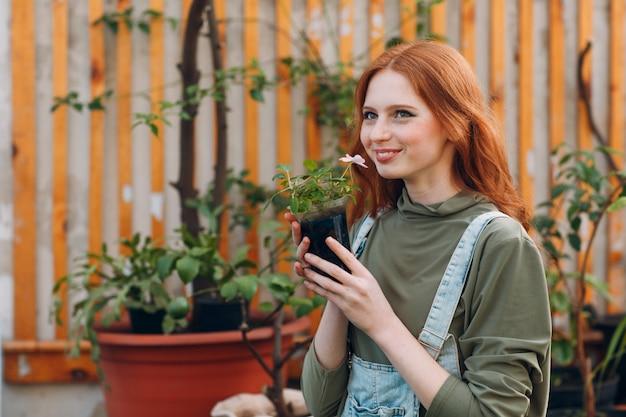 Tuinieren concept. jonge mooie vrouwen ruikende bloem in pot. de lente.