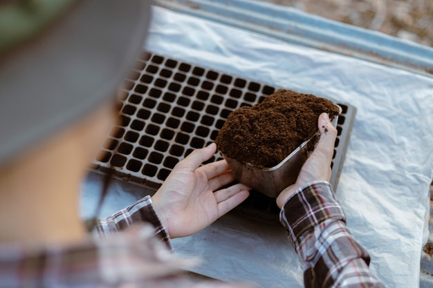 Tuinieren concept twee hand van een tuinman die rijke zwarte aarde in de kwekerij brengt en zich voorbereidt op het kweken van zaailingen.