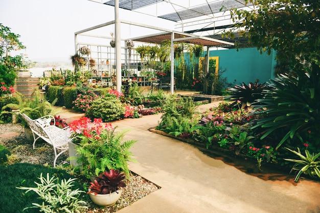 Tuinieren en decoreren van binnenkasomgevingen zet bloemen en planten op - ontspannen in een prachtige tuin met stoelen aan de buitenkant van het huis