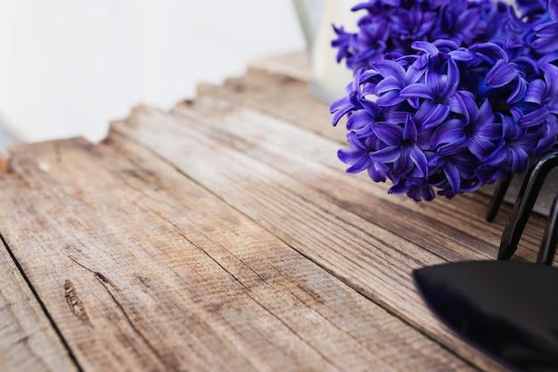 Tuinieren hobby concept. blauwe paarse hyacint bloem bloesem, kleine tuin hooivork of hark en schop op oude houten tafel achtergrond