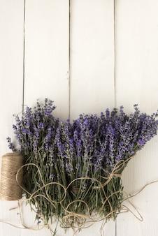 Tuinieren in de provence. op de retro tafel ligt een pittige paarse lavendel teruggewikkeld met decoratief draad. bovenaanzicht
