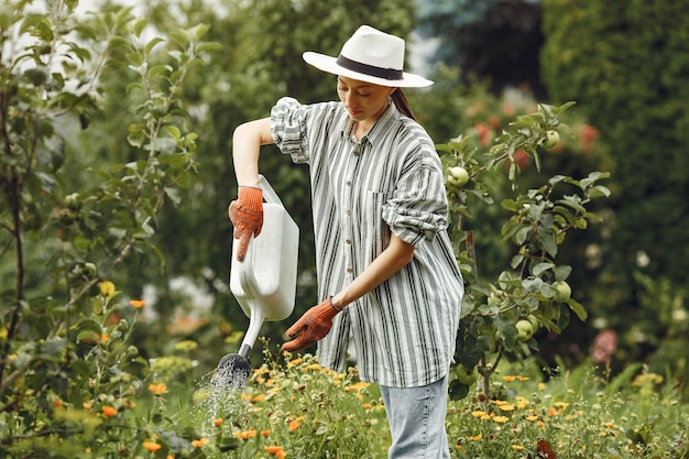 Tuinieren in de zomer. vrouw bloemen met een gieter water geven. meisje met een hoed.