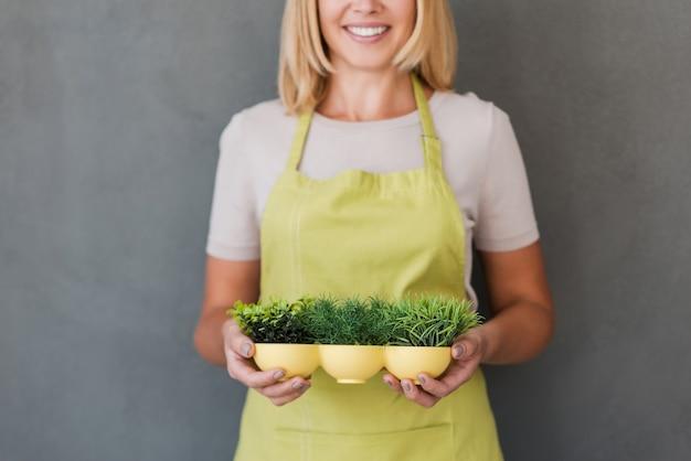 Tuinieren is meer dan hobby. bijgesneden afbeelding van vrolijke volwassen vrouw in groene schort