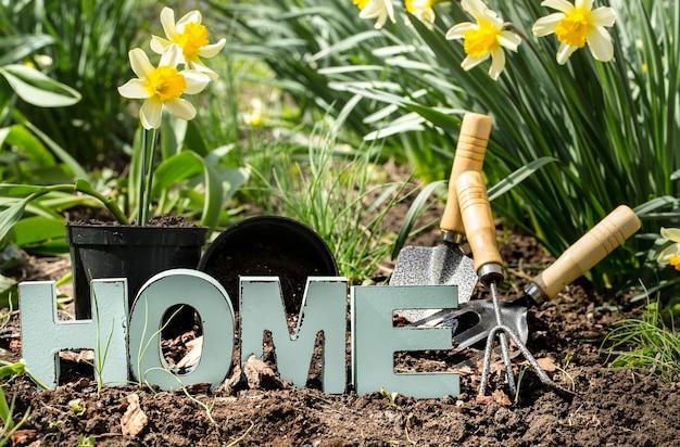 Tuinieren, lente bloemen gele narcissen met tuin benodigdheden. dag van de aarde. houten letters met het opschrift huis.