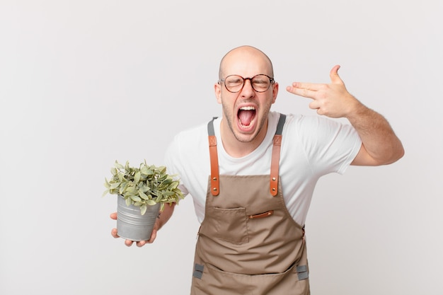 Tuinman die er ongelukkig en gestrest uitziet, zelfmoordgebaar maakt een pistoolteken met de hand, wijzend naar het hoofd