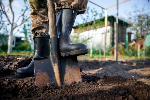 Tuinman graven in de tuin. grond die voorbereidingen treft voor aanplant in het voorjaar tuinieren.