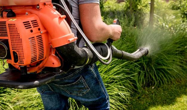 Tuinman in beschermend masker en glazen spuiten giftige pesticiden bomen