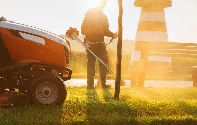 Tuinman maait het gazon in de vroege ochtend bij zonsopgang. onderhoud van het gazon. Premium Foto