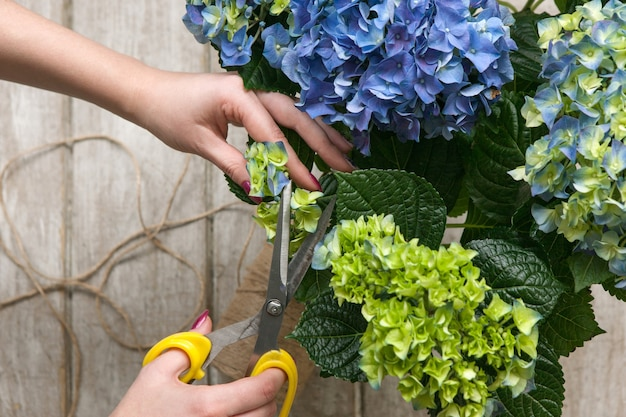 Tuinman maakt een boeket kasbloemen. de bloemist werkt in een kas met een paars boeket. floristiek workshop, vaardigheid, decor, klein bedrijfsconcept