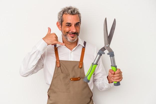 Tuinman man van middelbare leeftijd met een schaar geïsoleerd op een witte achtergrond met een mobiel telefoongesprek gebaar met vingers.