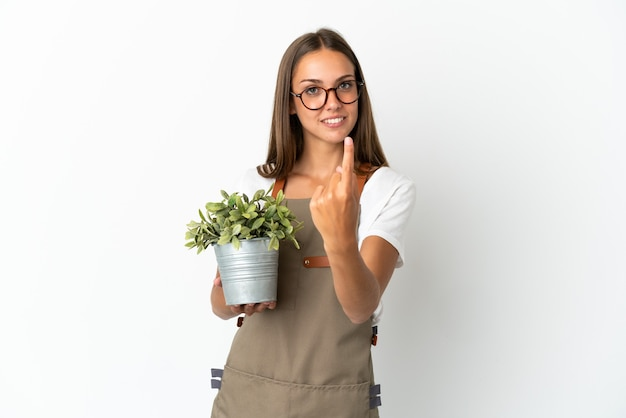 Tuinman meisje met een plant geïsoleerd doen komend gebaar