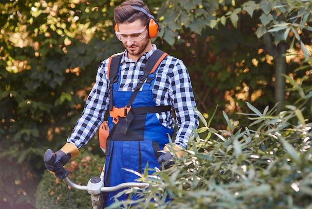 Tuinman met bril en koptelefoon met behulp van weedwacker