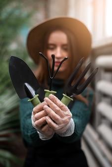 Tuinman met tuingereedschap in handen.