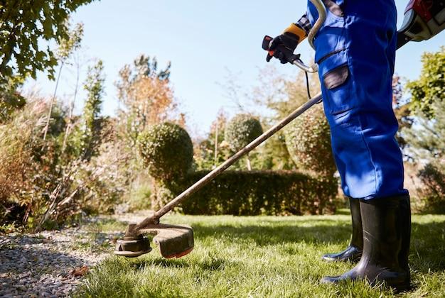 Tuinman met weedwacker die het gras in de tuin snijdt