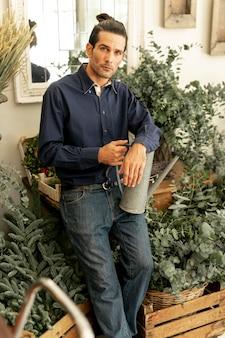 Tuinman omringd door planten met een gieter