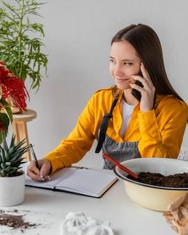 Tuinman praten aan de telefoon met een klant