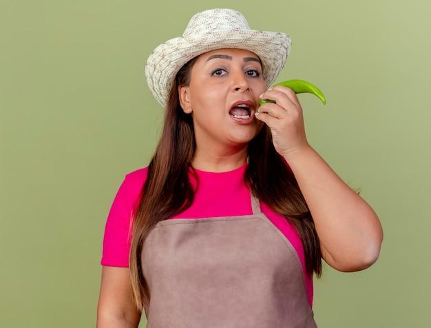 Tuinman van middelbare leeftijd die in schort en hoed groene hete spaanse peperpeper houdt