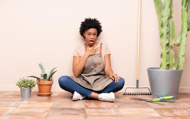 Tuinman vrouw zittend op de vloer rond planten