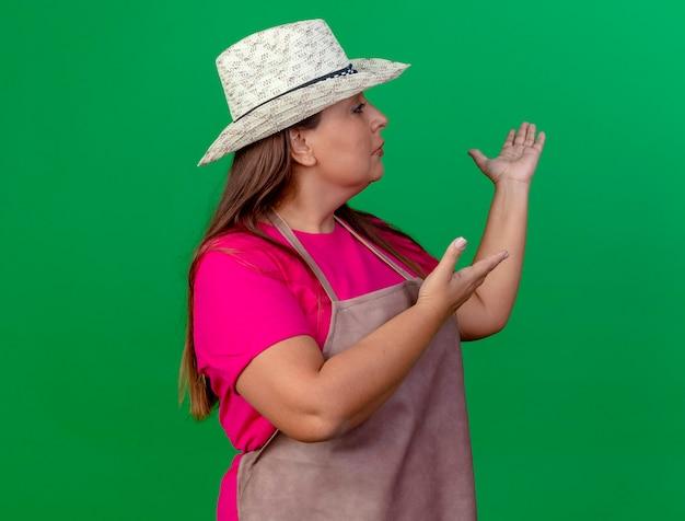 Tuinmanvrouw van middelbare leeftijd in schort en hoed die iets voorstellen