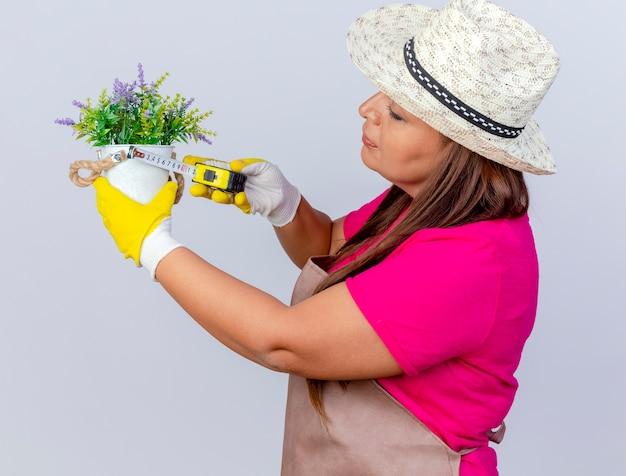 Tuinmanvrouw van middelbare leeftijd in schort en hoed die rubberhandschoenen draagt