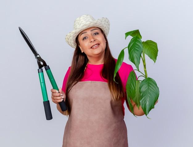 Tuinmanvrouw van middelbare leeftijd in schort en hoed met plant en heggenschaar die er zelfverzekerd glimlachend uitziet