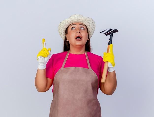 Tuinmanvrouw van middelbare leeftijd in schort en hoed met rubberen handschoenen die een minihark vasthouden die omhoog wijst en de wijsvinger verrast is