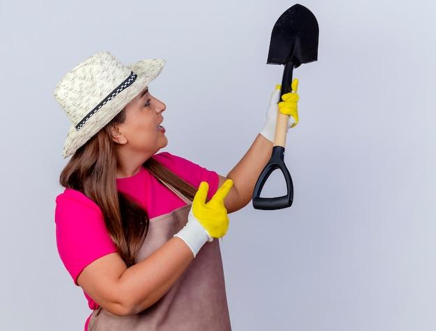 Tuinmanvrouw van middelbare leeftijd in schort en hoed met rubberen handschoenen die een schop vasthoudt en ernaar kijkt geïntrigeerd wijzend met de vinger ernaar