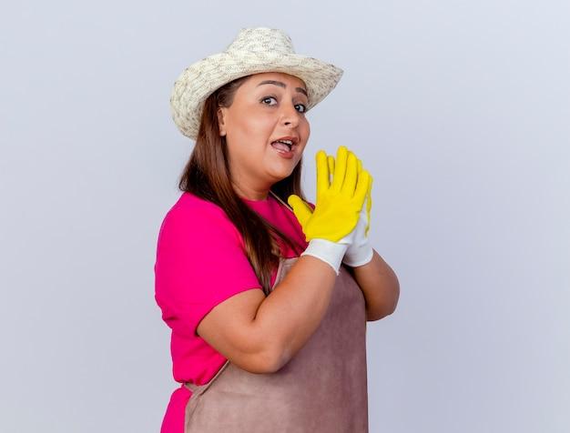 Tuinmanvrouw van middelbare leeftijd in schort en hoed met rubberen handschoenen die handen bij elkaar houden en vrolijk glimlachen