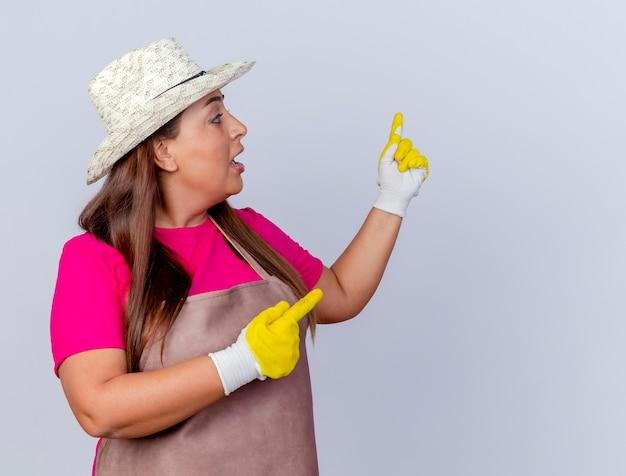 Tuinmanvrouw van middelbare leeftijd in schort en hoed met rubberen handschoenen die naar iets terug wijst en er verbaasd uitziet
