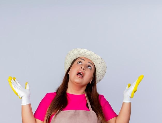 Tuinmanvrouw van middelbare leeftijd in schort en hoed met rubberen handschoenen die opkijkt met opgeheven handen die verward zijn