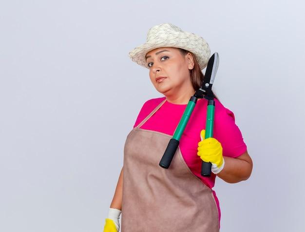 Tuinmanvrouw van middelbare leeftijd in schort en hoed met rubberen handschoenen met heggenschaar die naar de camera kijkt met een serieus gezicht