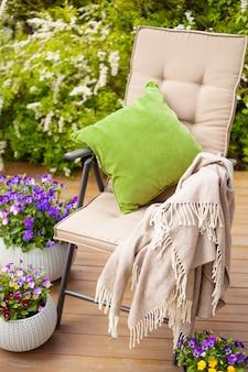 Tuinstoel op terras in zonlicht, viooltjebloemen
