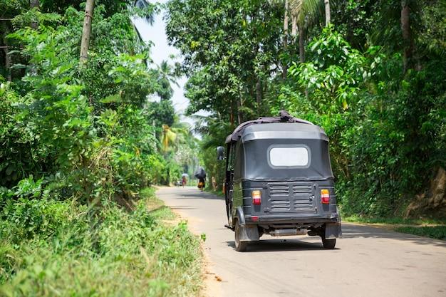 Tuk tuk op weg van sri lanka, achteraanzicht. tropisch woud van ceylon en traditioneel toeristenvervoer