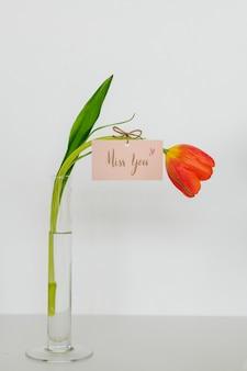 Tulp met een miss you tag in een vaas