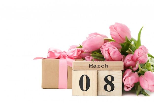 Tulpen, cadeau en houten kalender op wit, ruimte voor tekst