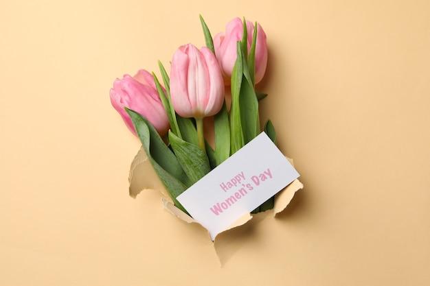 Tulpen en tekst happy women's day door gat in beige papier