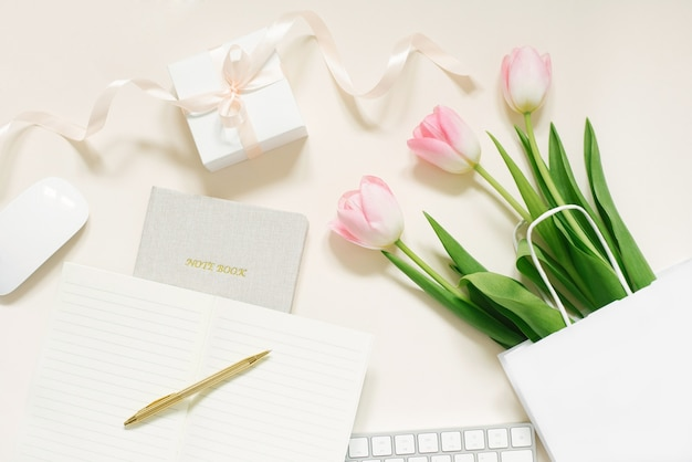 Tulpen, geschenkdoos en koffie op een beige achtergrond. plat leggen. 8 maart, internationale vrouwendag. valentijnsdag. blogger's werkplek