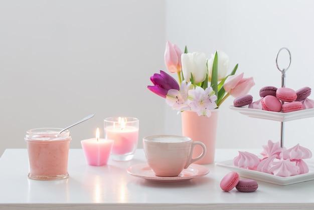 Tulpen in vaas en kopje koffie met dessert