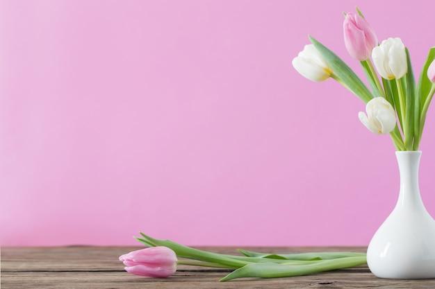 Tulpen in witte vaas op roze
