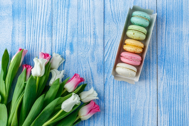 Tulpen met bitterkoekjes op blauwe houten oppervlak