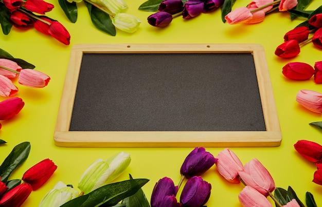 Tulpen op houten lijst met zwart leeg schoolbord