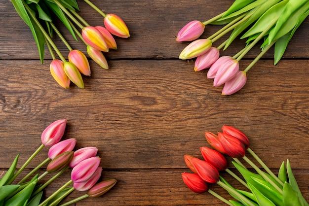Tulpen van verschillende kleuren op houten tafel, met frame in de middelste kopie ruimte