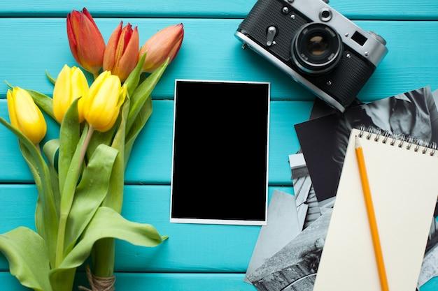 Tulpen, vintage retro camera en kladblok.