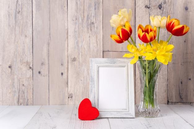 Tulpenbloem in glasvaas over houten lijstmuur als achtergrond voor het ontwerpconcept van de moederdag.